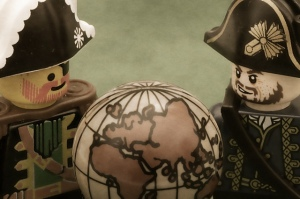 toy pirates looking at a globe